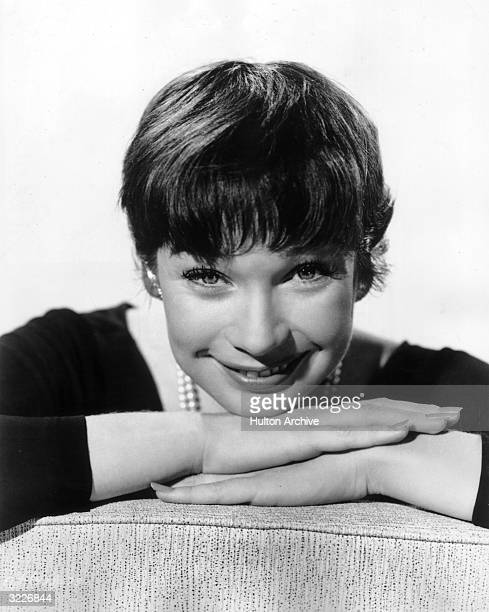 Promotional headshot portrait of American actor Shirley MacLaine smiling with her chin resting on her hands for director Billy Wilder's film 'The...
