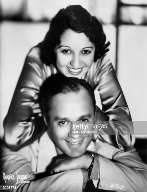 Promotional headshot portrait of American comedian Jack Benny and his wife, Mary Livingstone, leaning on his shoulders, both smiling, taken for a...