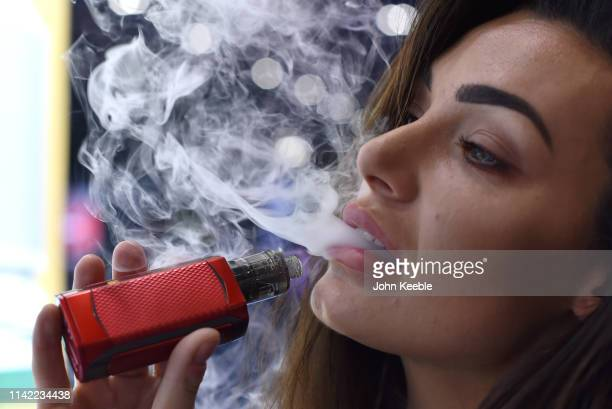 Promotional person Tanya Atherton vapes on the Reds Ejuice stand during Vape Jam 2019 at ExCel on April 12 2019 in London England Vape Jam UK the...