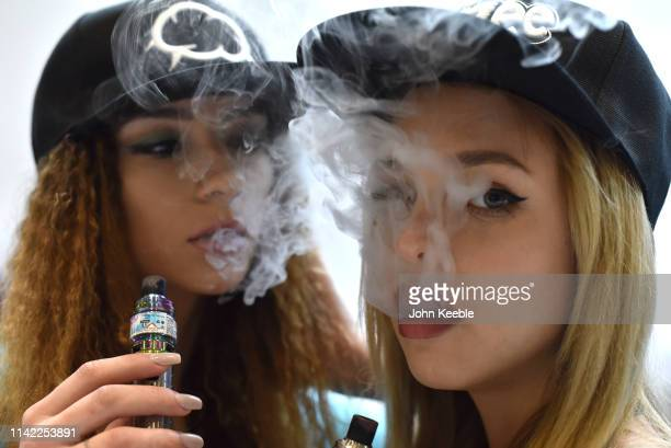 Promotional persons Flori Neagu and Anna Mukonina vape on the Eliquid France Fruizee stand during Vape Jam 2019 at ExCel on April 12 2019 in London...