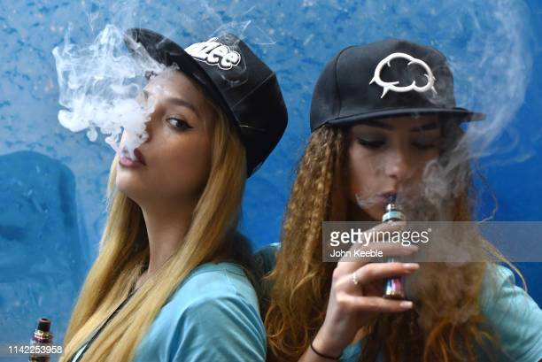 Promotional persons Anna Mukonina and Flori Neagu vape on the Eliquid France Fruizee stand during Vape Jam 2019 at ExCel on April 12 2019 in London...