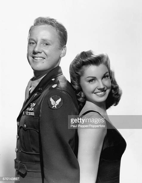 Promotional portrait of actors Van Johnson and Esther Williams standing back to back as they appear in the film 'Thrill of a Romance' 1945