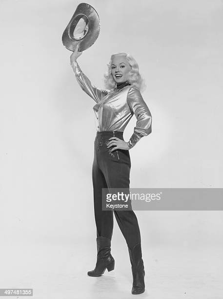 Promotional portrait of actress Mamie Van Doren, wearing a cowgirl costume, circa 1955.