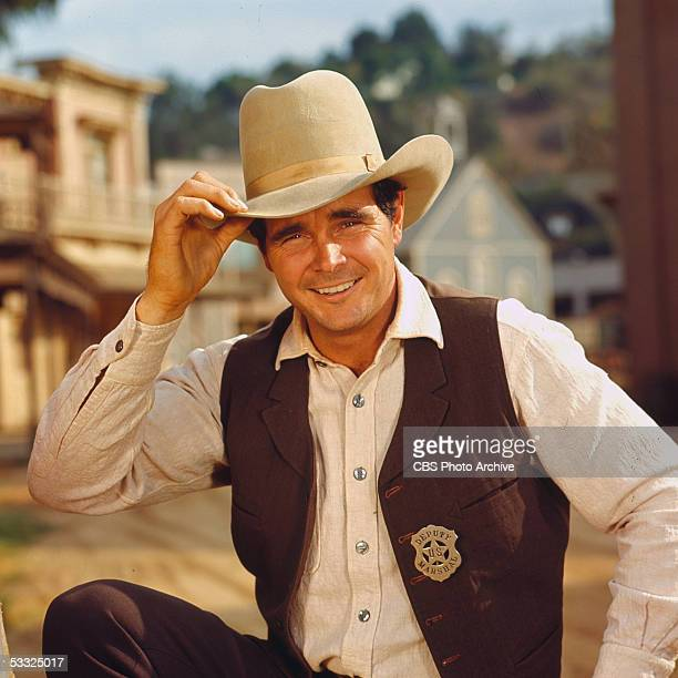 Promotional portrait of American actor Buck Taylor as he tips his hat while in costume as Newly O'Brien on the set of the television series...