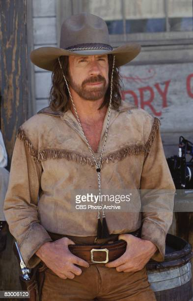 Promotional portrait of American actor Chuck Norris as he poses in a fringed shirt, gun belt, and stetson for an episode the television series...