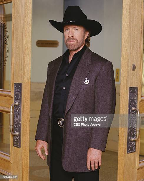 Promotional portrait of American actor Chuck Norris , dressed in a blazer over a black satin shirt and a black stetson, as he poses in a doorway for...