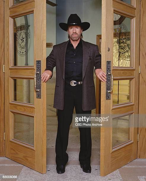 Promotional portrait of American actor Chuck Norris , dressed in a blazer over a black satin shirt and a black stetson, as he poses between two open...