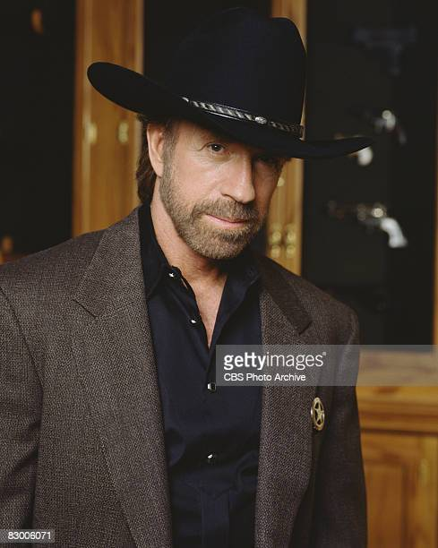 Promotional portrait of American actor Chuck Norris dressed in a blazer over a black satin shirt and a black stetson, as he poses for the television...