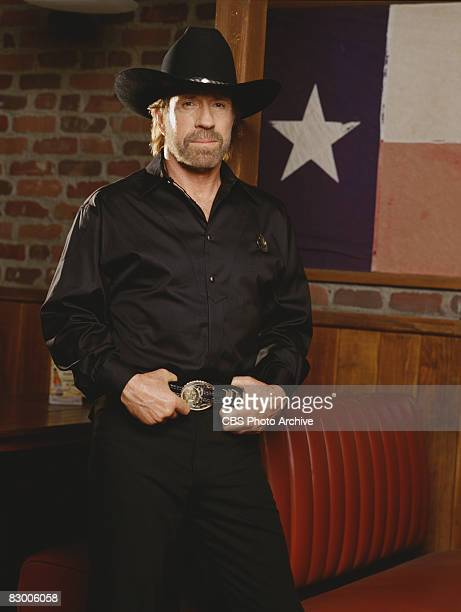 Promotional portrait of American actor Chuck Norris , dressed in a black satin shirt and a black stetson, as he poses with his hands on his belt for...