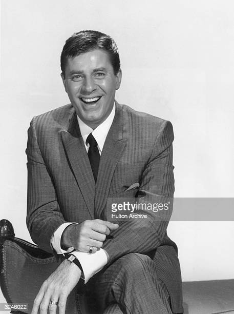 Promotional portrait of American actor director and comedian Jerry Lewis sitting on a divan as host of the television series 'The Jerry Lewis Show'