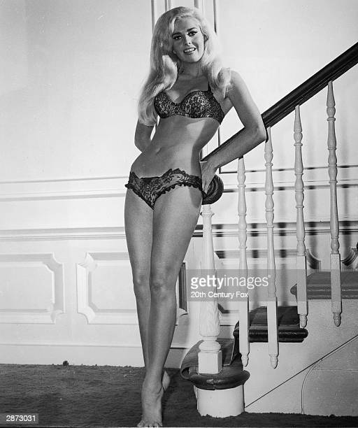 Promotional portrait of American actor Edy WiIlliams leaning aganist a staircase wearing a bra and panties in 'The Secret Life of an American Wife'...