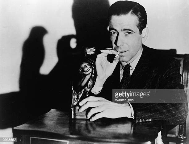 Promotional portrait of American actor Humphrey Bogart holding 'The Maltese Falcon' while smoking a cigarette, in the film directed by John Huston,...