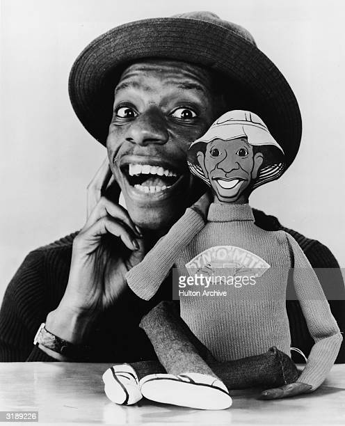 Promotional portrait of American actor Jimmie Walker as he poses with a talking doll based on his character 'J. J.' from the television series 'Good...
