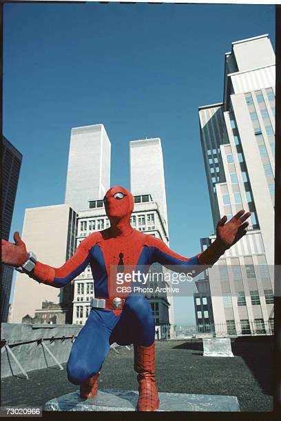 Promotional portrait of American actor Nicholas Hammond as the costumed superhero Spiderman as he crouches on the roof of a building near the World...