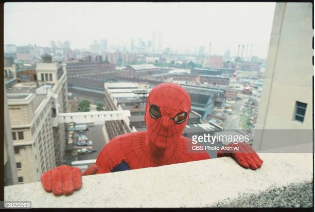 Promotional portrait of American actor Nicholas Hammond as the costumed superhero Spiderman as he peers over the edge of a window sill on the CBS...