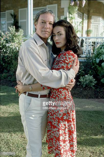 Promotional portrait of American actor Richard Chamberlain and British actress Amanda Donohoe as they embrace in a garden for the television...