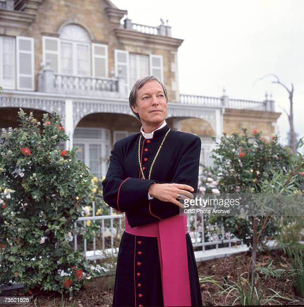 Promotional portrait of American actor Richard Chamberlain as he stands arms crossed and in costume in a garden on the set of the television...