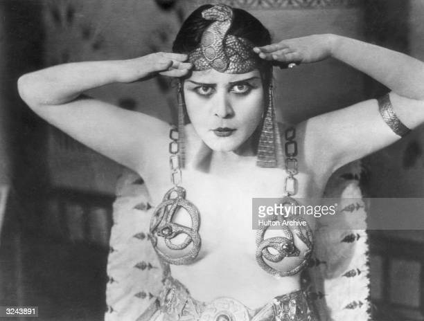 Promotional portrait of American actor Theda Bara wearing an Egyptian headdress and breast plates with a snake design for director J Gordon Edwards'...