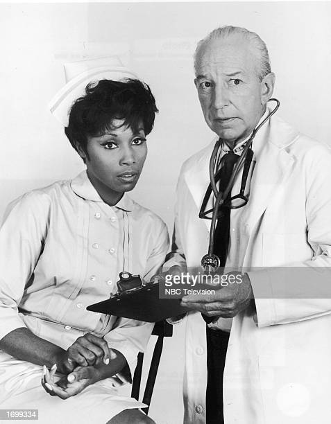 Promotional portrait of American actors Diahann Carroll and Lloyd Nolan in their nurse and doctor costumes for the television series 'Julia' circa...