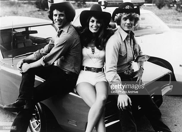 Promotional portrait of American actors Tom Wopat, Catherine Bach, and John Schneider sitting on the hood of the car, 'General Lee,' for the...