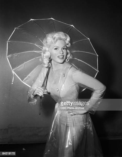 Promotional portrait of American actress and sex symbol Jayne Mansfield as she poses dressed in a transparent plastic raincoat and holds an umbrella...