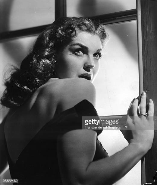 Promotional portrait of American actress and swimming champion Esther Williams as she stands at a window and startled looks over her shoulder for...