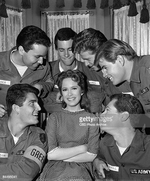 Promotional portrait of American actress Linda Henning as Betty Jo Bradley Elliot as she smiles while surrounded by unidentified actores dress as...