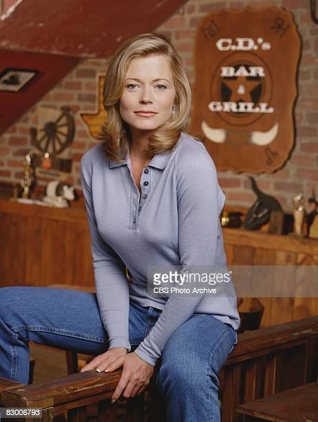 Promotional portrait of American actress Sheree J Wilson as she sits astride a railing on 'CD's Bar Grill' set for the television series 'Walker...