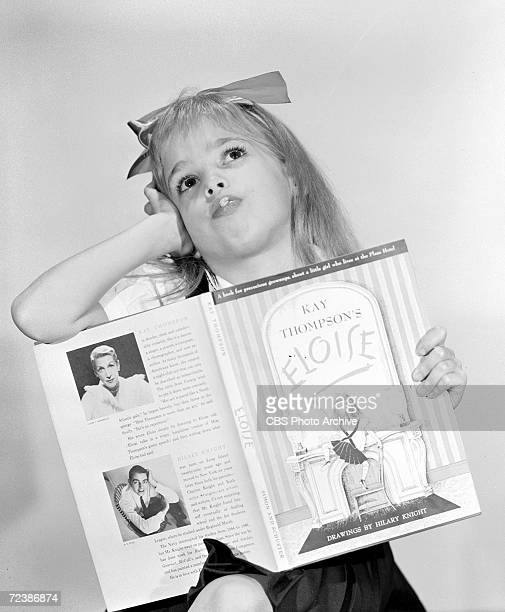 Promotional portrait of American child actress Evelyn Rudie, her head tossed back, as she holds a copy of the book 'Elosie,' in support of her role...