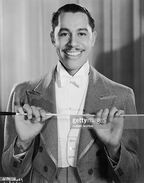 Promotional portrait of American jazz bandleader Cab Calloway holding a conductor's baton in front of his chest for director William Keighley's film...