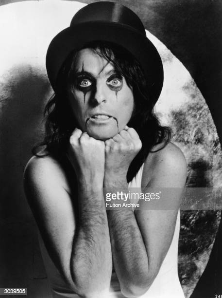 Promotional portrait of American rock singer and songwriter Alice Cooper wearing a top hat and makeup early 1970s
