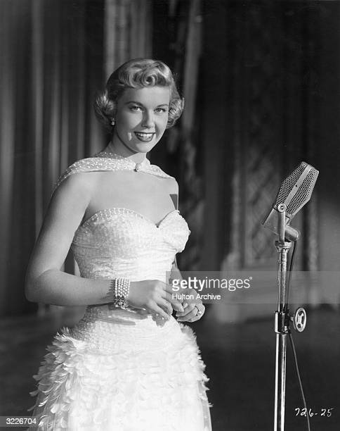 Promotional portrait of American singer and actor Doris Day smiling as she stands behind a microphone from director Michael Curtiz's film 'Young Man...
