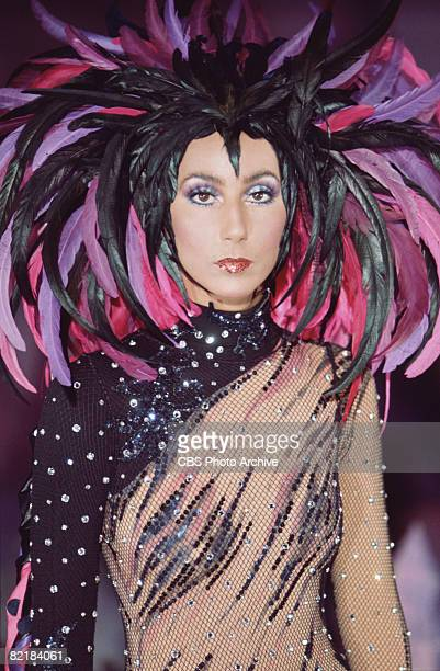 Promotional portrait of American singer and actress Cher in a semitransparent outfit with a feathered headdress for the television variety show 'The...