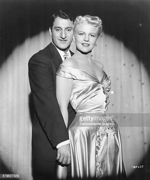 Promotional portrait of American singers Danny Thomas and Peggy Lee as they pose in front of a stage curtain circa 1950