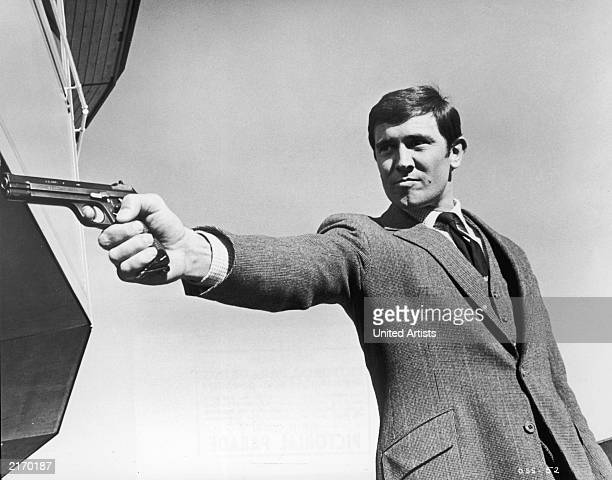 Promotional portrait of Australian actor George Lazenby aiming a gun for the James Bond film 'On Her Majesty's Secret Service' directed by Peter Hunt...