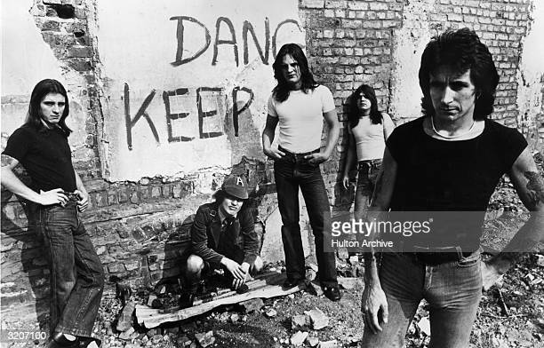 Promotional portrait of Australian hardrock group AC/DC standing in front of a graffiticovered brick wall drummer Phillip Rudd guitarist Angus Young...