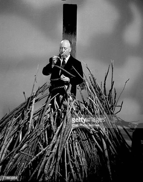 Promotional portrait of Britishborn American film and television director Alfred Hitchcock as he lights a cigarette while tied to a stake above a...