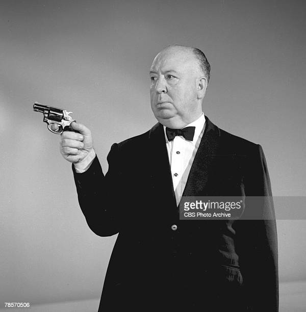 Promotional portrait of Britishborn American film and television director Alfred Hitchcock dressed in a tuxedo as he aims a revolver for his...