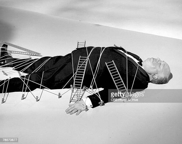 Promotional portrait of Britishborn American film and television director Alfred Hitchcock as he lies tied to pegs in the floor and covered with...