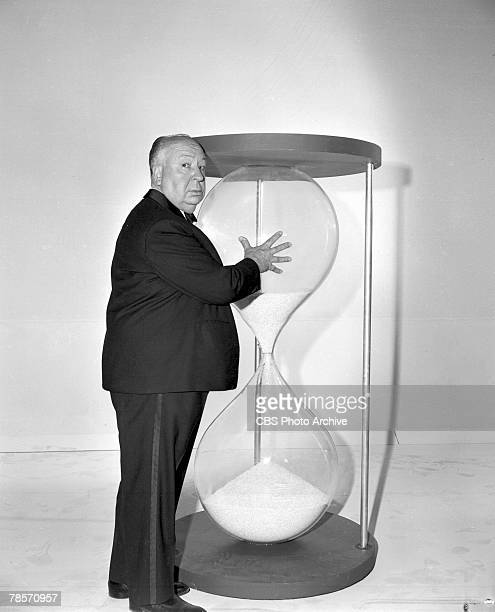 Promotional portrait of Britishborn American film and television director Alfred Hitchcock as he glances over his shoulder his hand on an oversize...