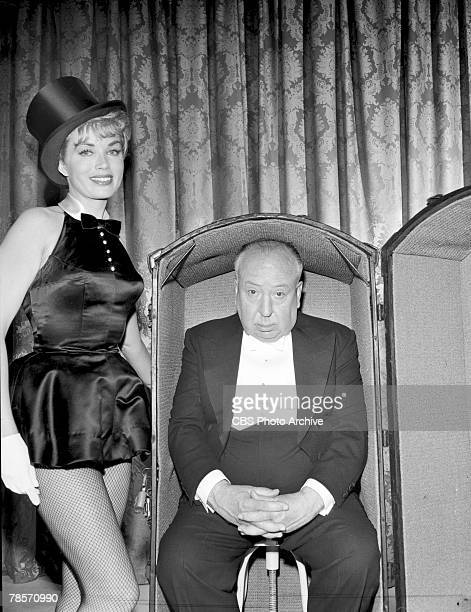 Promotional portrait of Britishborn American film and television director Alfred Hitchcock as he sits on a stool inside an open steamer trunk next to...