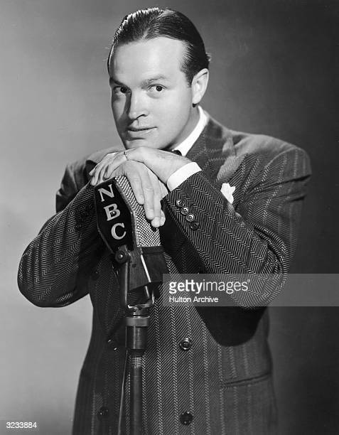 Promotional portrait of British-born entertainer Bob Hope wearing a herringbone suit and posing with his hands over an NBC radio microphone.