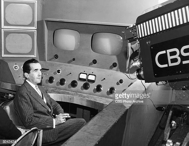 Promotional portrait of broadcast journalist Edward R Murrow smoking a cigarette in front of a CBS television camera