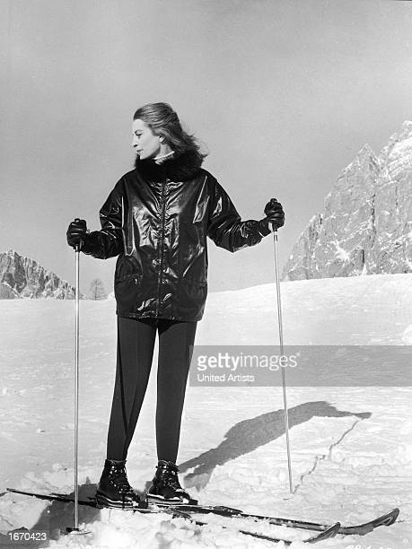 Promotional portrait of French actor Capucine wearing wool leggings a fur trimmed vinyl jacket and skiis on a ski slope for the film 'The Pink...