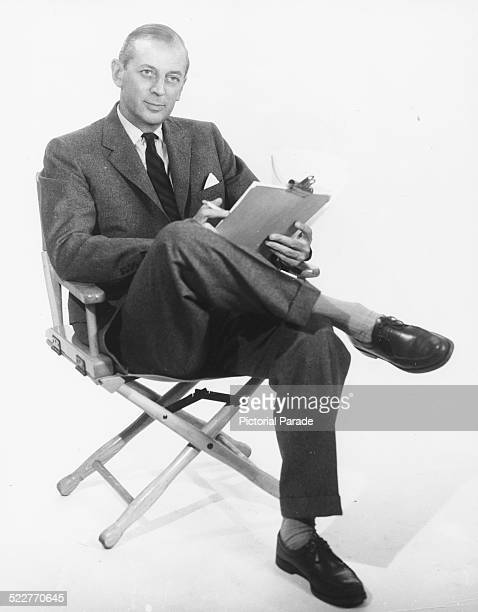 Promotional portrait of journalist and broadcaster Alistair Cooke holding a clipboard and sitting in a chair for ABC Television circa 1950