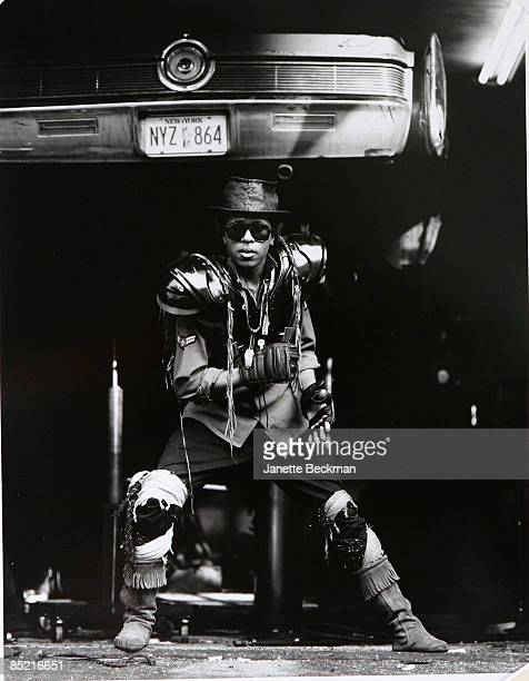 Promotional portrait of New York based hiphop artist Strafe as he poses in an elaborate costume under a car raised on a garage jack New York New York...