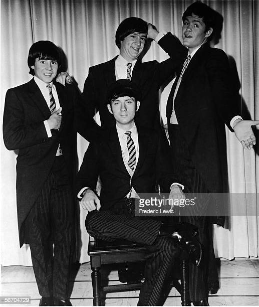 Promotional portrait of popular music and television group the Monkees as they pose infront of a curtain, dressed in tail coats and pin-stripe...