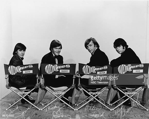 Promotional portrait of popular music and television group the Monkees dressing in tuxedos and they as they sit in folding chair and look over their...