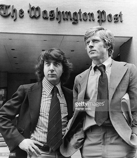 1976 Promotional portrait of Robert Redford right and Dustin Hoffman standing in front of the Washington Post Building in a still from director Alan...