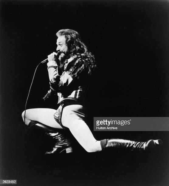 Promotional portrait of Scottish musician and singer Ian Anderson of the group Jethro Tull singing into a microphone on stage and resting on one knee...